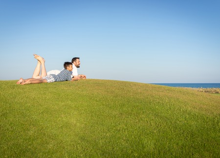 grass and sky: Happy summer vacation for father and son on green meadow near sea