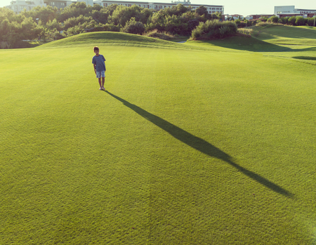 teen golf: Kids with their shadows on grass