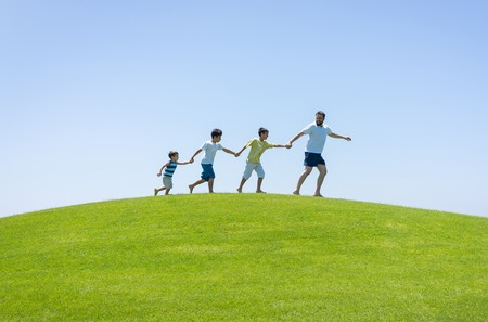 teach: Happy summer vacation for family on green meadow near sea
