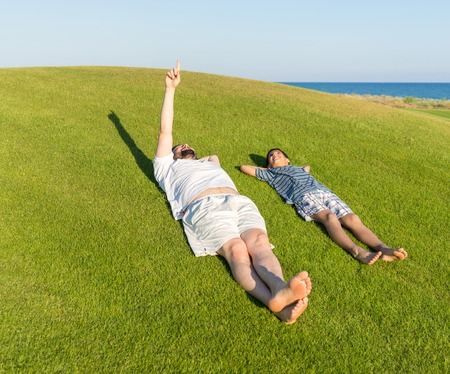 Happy summer vacation for father and son on green meadow near sea