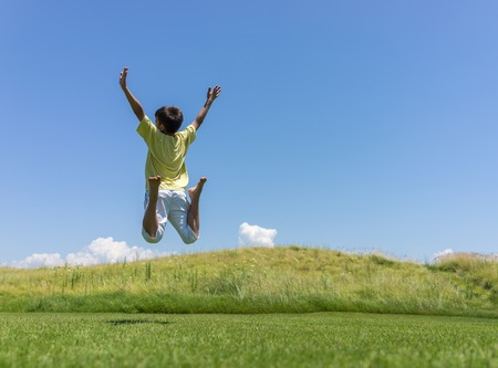 family outside: Kid jumping on beautiful field Stock Photo
