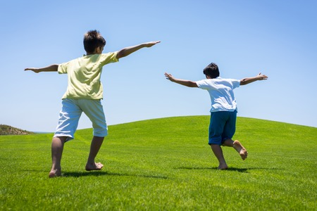 green park: Happy summer vacation for kids on green meadow near sea Stock Photo