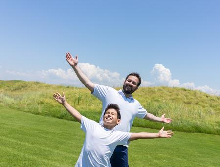 teen golf: Vacaciones de verano feliz de padre e hijo en el prado verde cerca del mar Foto de archivo