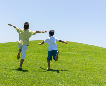 sports field: Happy summer vacation for kids on green meadow near sea Stock Photo