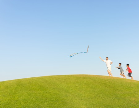 kids outside: Running with kite on summer holiday vacation, perfect meadow and sky on seaside