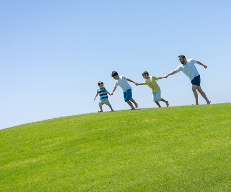 children background: Happy summer vacation for family on green meadow near sea