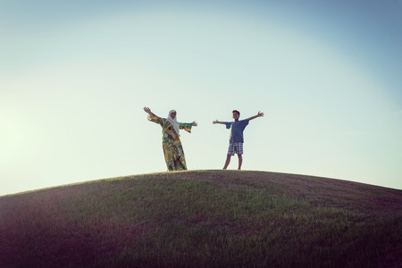 arab spring: Muslim woman and son silhouette