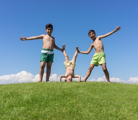 cabeza abajo: Hermanos jugando boca abajo en el prado verde Foto de archivo