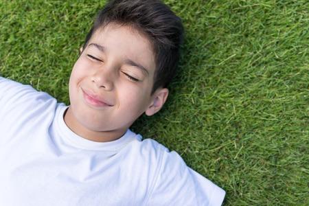 niños sonriendo: Vacaciones de verano feliz para los niños en el prado verde cerca del mar