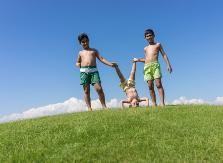 upside down: Brothers playing upside down on green meadow
