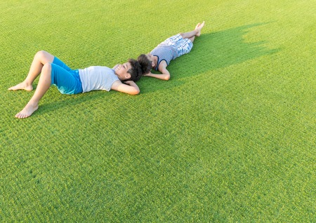 lying on grass: Happy summer vacation for kids on perfect meadow grass