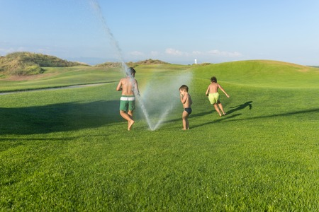 teen golf: Happy summer vacation for kids on green meadow splash sprinkle water