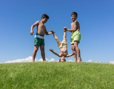hermanos jugando: Hermanos jugando boca abajo en el prado verde Foto de archivo