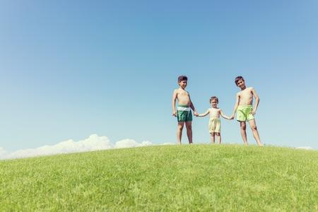 brothers playing: Hermanos jugando boca abajo en el prado verde Foto de archivo