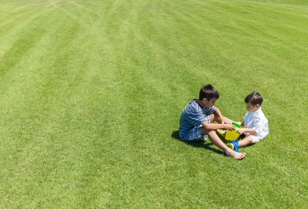 Happy summer vacation for kids on green meadow near sea Stock Photo