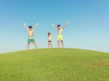 teen golf: Vacaciones de verano feliz para los ni�os en el prado verde cerca del mar