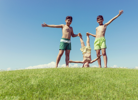 al reves: Brothers playing upside down on green meadow
