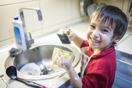 A little cute boy washing dishes