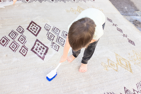 Kid cleaning carpet Stock Photo
