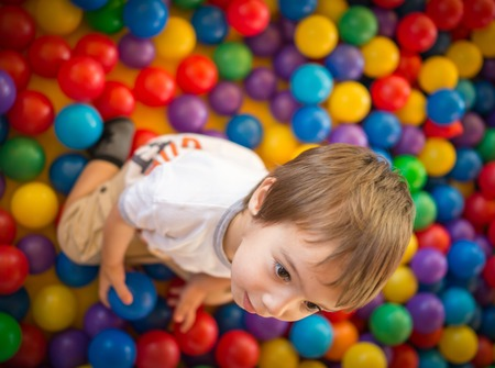 playcentre: Happy cute child playing and having fun at kindergarten with colorful balls