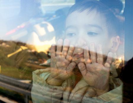 Little boy looking through window Standard-Bild