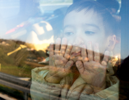 Little boy looking through window Imagens