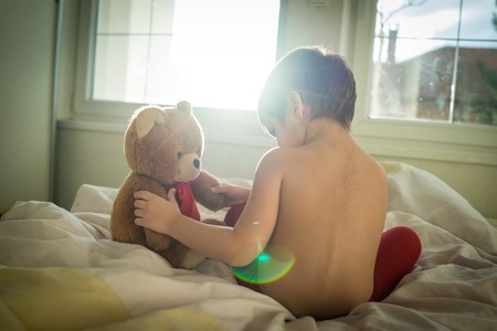 home life: A little cute kid with Teddy bear in bedroom