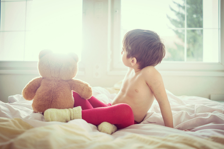 child in bed: A little cute child with Teddy bear on the bed