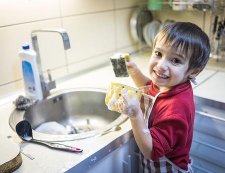 gospodarstwo domowe: A little cute boy washing dishes