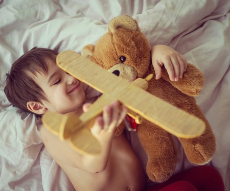 wooden toy: Happy kid playing with wooden toy airplane and Teddy bear in bedroom