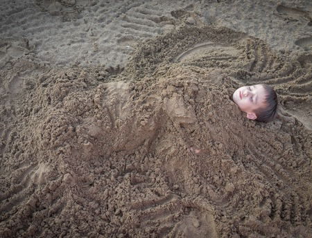 boys playing: Cute kid burried in the sand for fun