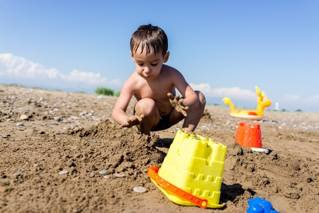 boy kid: Playful kids on summer beach sand vacation having fun and happy time Stock Photo