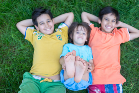 young boys: Group of cute happy children in summer lying on green grass with feet up Stock Photo
