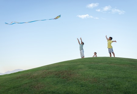 flying kite: Little boy on summer vacation having fun and happy time flying kite on the sea beach Stock Photo