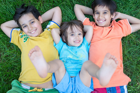 brothers: Group of cute happy children in summer lying on green grass with feet up Stock Photo