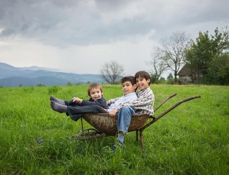Glückliche Kinder auf dem Feld mit Wagen spielen