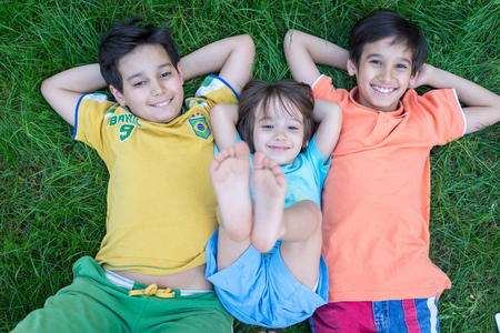 child laughing: Group of cute happy children in summer lying on green grass with feet up Stock Photo