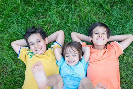 laying down: Group of cute happy children in summer lying on green grass with feet up Stock Photo