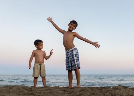 Los niños pequeños en la diversión de la playa abarrotada