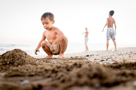 Kids playing in beach sand photo