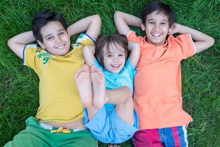 Group of cute happy children in summer lying on green grass with feet up photo