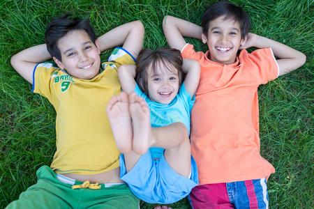 Grupo de niños felices lindo en verano tumbado en la hierba verde con los pies en alto