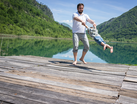 Dad and son playing on the mountain lake Stock Photo