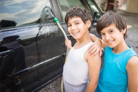 young boys: Young father and little boys washing car in summer day Stock Photo