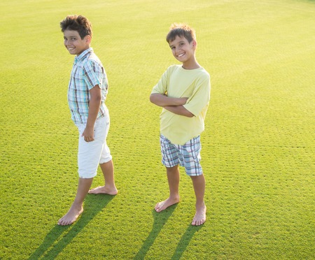 child boy: Kids on beautiful green meadow with long shadows