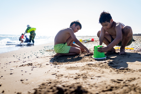 child boy: Playful kids on summer beach sand vacation having fun and happy time Stock Photo