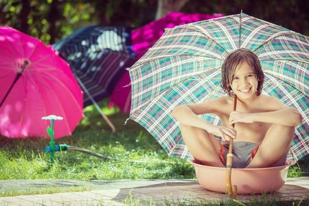 Happy kids on summer meadow splashing water using umbrella for having fun and happy time