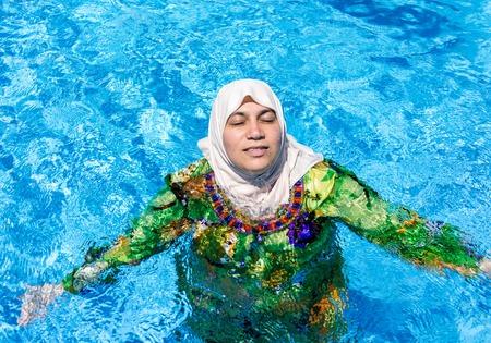 Muslim Arabic woman with burkini in pool photo