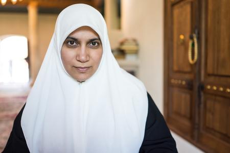Muslim woman reading Koran and praying in mosque photo