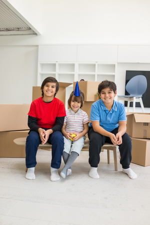 boite carton: Happy kids with boxes at new modern home top view